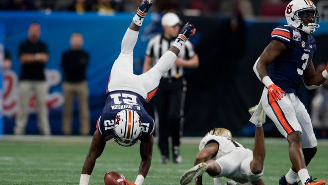 UCF defensive back Mike Hughes tackles Auburn running back Kerryon Johnson in the Peach Bowl.