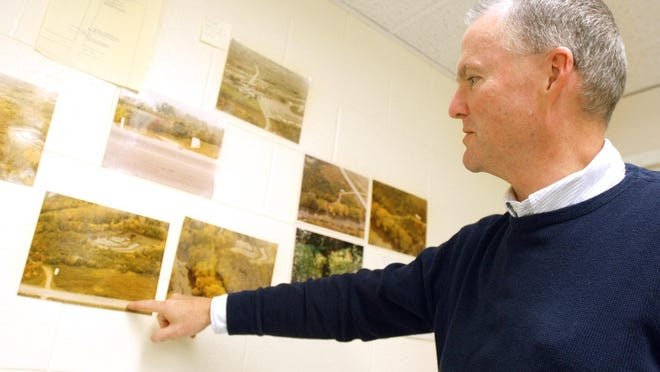 James Helmer, chief investigator with the District Attorney's Office, points to aerial photos hanging in the task force office in 2009. The photos were of the surrounding area where Kim Simon's body was found. Helmer is now retired and says he's still haunted by the case.