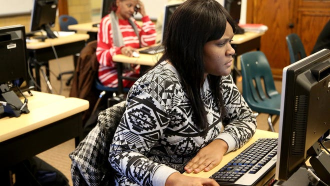 Kelly West works on her English skills during GED classes at the Adult Education Center-West Campus in January 2015. Scoring changes will make it easier for people to pass the GED.