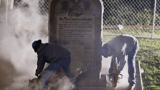 Concrete dust flies as workers remove the controversial Ten Commandments monument from its base on the grounds of the state Capitol in Oklahoma City on Oct. 5.