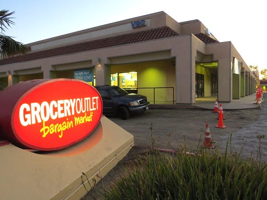 A lighted sign for Grocery Outlet Bargain Market marks the driveway from South Petit Avenue in Ventura. The shopping center's parking lot is being replaced prior to the store's soft opening on Nov. 9.