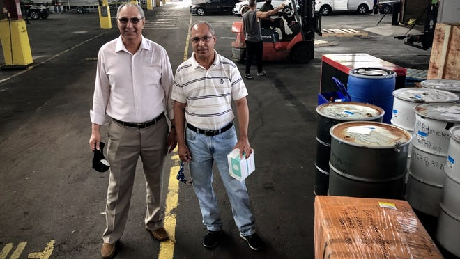 Victor DePina, left, president and CEO of Atlantic Shipping Company, and his brother John De Pina, vice president of operations, are seen here in the state pier in Fall River where they store and ship cargo to Cape Verde and Haiti.