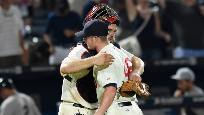 Atlanta Braves catcher Evan Gattis (24) and relief pitcher Craig Kimbrel (46) react after defeating the Oakland Athletics at Turner Field.