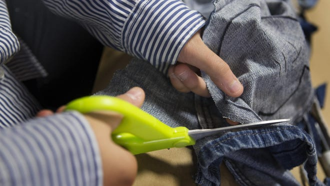 """A volunteer cuts pattern pieces that will be made into shoes for children in Uganda. The United Methodist Church in Madison held a """"Sole Cutting Party"""" on Nov. 22."""