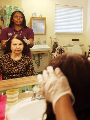 Celeste Cayton, 24, of Detroit does the hair of her client Elizabeth Kertesz-Hacket at her Royal Oak home Wednesday, Oct. 29, 2014.