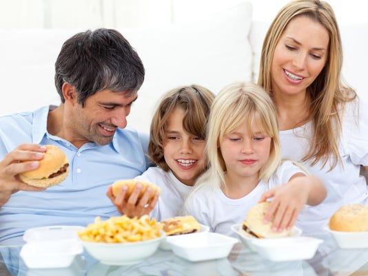 Joyful family eating hamburgers