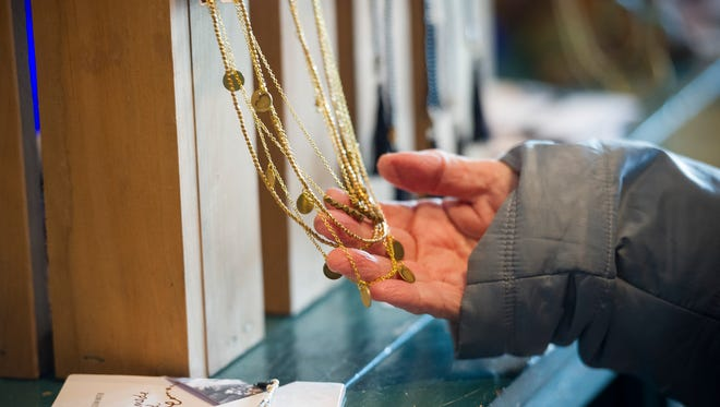 Lynn Hert, of Newburgh, looks through handmade jewelry at Amerie during Small Business Saturday in Newburgh, Nov, 26, 2016. Independent businesses throughout the country take part in the annual event.