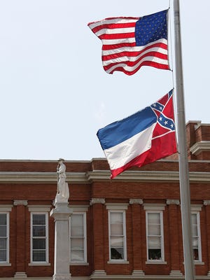 The American flag and Mississippi state flag fly at half staff outside the Forrest County Courthouse in Hattiesburg, Miss., Monday, May 11, 2015, in honor of Hattiesburg police officers Benjamin Deen and Liquori Tate, who were shot to death Saturday night. Four people have been arrested and charged in their deaths and are to make their initial court appearance on Monday afternoon.
