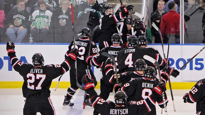 St. Cloud State University players celebrate an overtime goal by Judd Peterson giving them the 3-2 victory over Michigan Tech during Friday's NCAA West Regional Ice Hockey Tournament at Scheels Arena in Fargo, N.D.