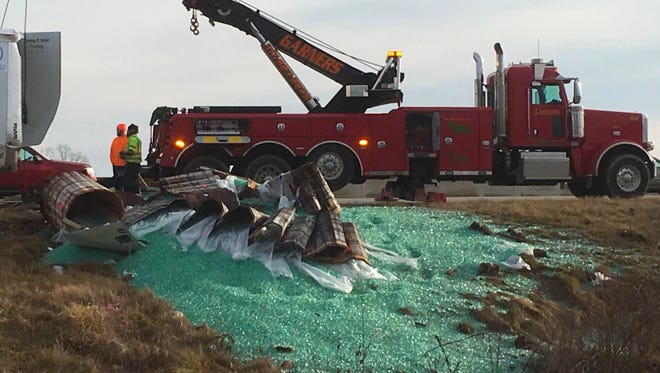 A tow truck helps clean up the spill of marbles from a semi on I-465 on Saturday, Jan. 21, 2017.