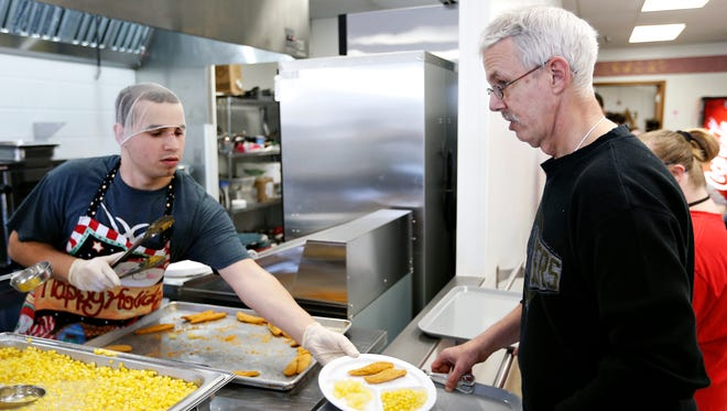Austin Arnold (left) serves lunch to Kenny Hall, a SWI Industrial Solutions employee, at the company's cafeteria in Springfield on Dec. 23, 2015. SWI Industrial Solutions has started a program to provide lunch for their employees, most of whom have a disability.