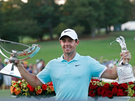 FILE - In this Sept. 25, 2016, file photo, Rory McIlroy poses with the trophies after winning the Tour Championship golf tournament and the FedEX Cup at East Lake Golf Club, in Atlanta. Along with revamping the PGA Tour schedule in two years, this would be a great time to change the format for the FedEx Cup. One plan under discussion with the players is to separate the Tour Championship from one final day worth $10 million to the winner.  (AP Photo/John Bazemore, File)