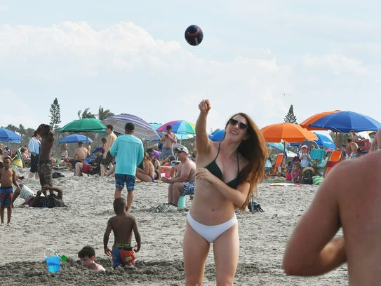 Amber Sumpter and Troy Bowman toss a football on the beach at Cocoa Beach, near Minutemen Causeway.