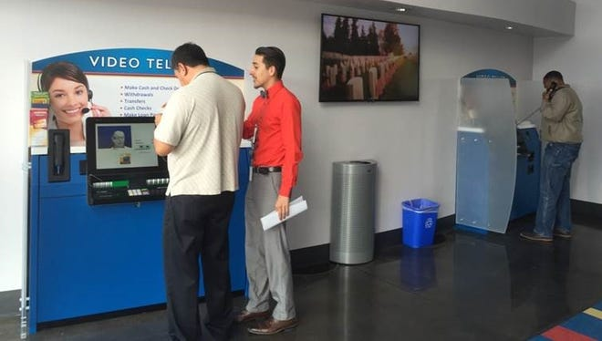 A customer is shown how to operate the interactive video teller inside First Light Federal Credit Union's new Fort Bliss branch.