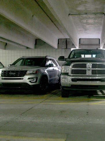 Pickups and SUVs are parked in a downtown Detroit parking