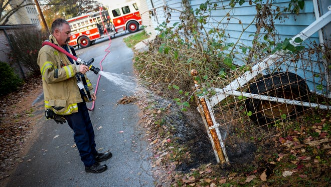 Capt. Steve Mendoff of the Lebanon City Fire Department waters down the area of a reported leaf fire along a fence at 503 Laurel St. in the City of Lebanon on November 17, 2015.