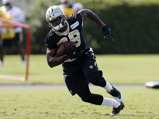 This July 28, 2017 photo shows New Orleans Saints running back Adrian Peterson (28) running with the ball during an NFL football training camp in Metairie, La. Peterson is still waiting to show off the renowned physical aspect of his game with his new team because there has been only minimal tackling allowed at Saints training camp so far. Still, he appears healthy and his presence has New Orleans' offense optimistic about the dynamic he'll add to an already potent scheme. (AP Photo/Jonathan Bachman)
