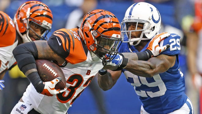 Cincinnati Bengals running back Jeremy Hill fights for yardage against the Indianapolis Colts strong safety Mike Adams during the fourth quarter of their game at Lucas Oil Stadium in Indianapolis, Sunday Oct. 19.