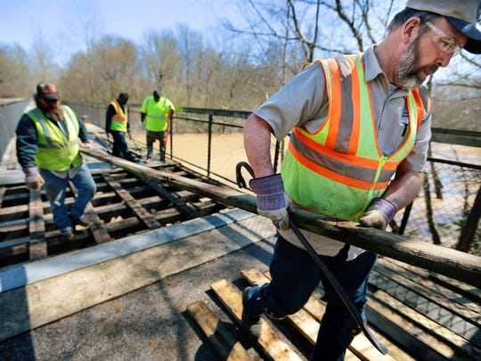 James Riley (right) and Arch LaComb help remove planks from the Shelby Farm Greenline's bridge over the Wolf River Monday afternoon. Warmer weather notwithstanding, a section of the multi-use trail is closed this week to allow for maintenance work on the bridge.