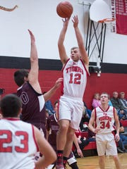 Fannett-Metal's Lucas Wingert (12) takes a shot while Souther Fulton's Brandon Lynch (00), rleft, tries to block the shot during a boys basketball game on Friday, Jan. 13, 2017 at Fannett-Metal. Southern Fulton defeated Fannett-Metal 72-38.