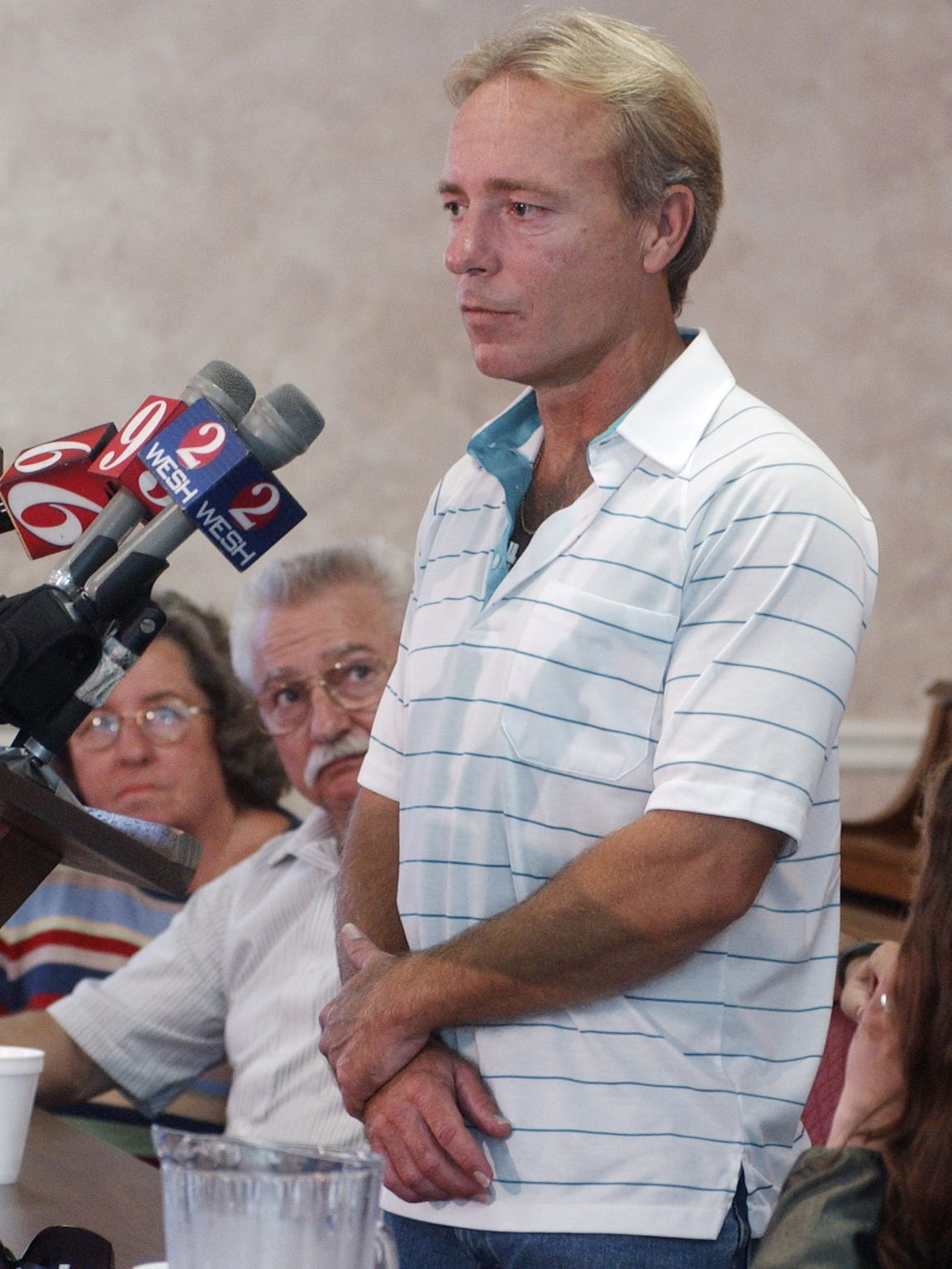 FILE: 8/12/04--Wilton Dedge, set free from jail, holds a press conference at First Baptist Church of Cocoa, with attorneys, and his family. In the background, watching him address the media, are his parents, Mary, and Gary.