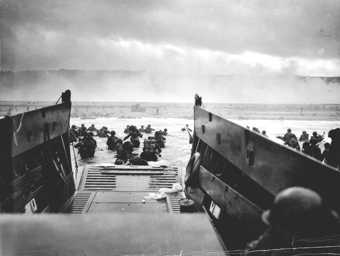 """A LCVP (Landing Craft, Vehicle, Personnel) from the U.S. Coast Guard-manned USS Samuel Chase disembarks troops of the U.S. Army's First Division on the morning of June 6, 1944 (D-Day) at Omaha Beach.  """"The wreckage was vast and startling. The awful waste and destruction of war"""""""