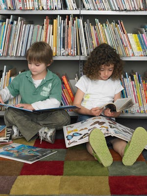 Boy and girl reading in library