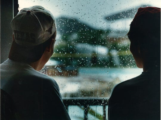 Chris Anderson (left) and Russ Allen (right) inside the lobby of the Port Royal condominium where many spring breakers are staying, look on as raindrops fall on the window March 16, 1994. Most of the other spring breakers were partying in their rooms, they said.