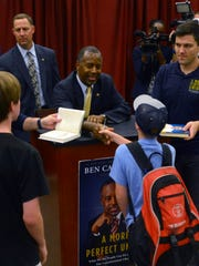 "Presidential candidate Ben Carson greets visitors Sunday during his book signing ""A More Perfect Union"" at Books-A-Million in Pensacola."