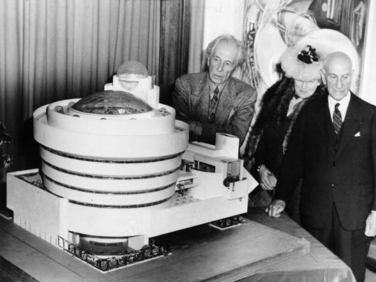 Frank Lloyd Wright, left, looks over his spiral-shaped