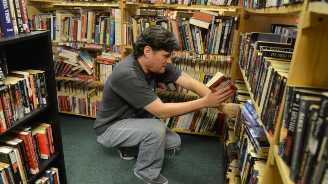 Surrounded by books, Tom Schafer is busy restocking the shelves Tuesday at the Book Exchange in Port Clinton.
