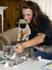 Linda Reichel, who operates a not-for-profit animal rescue group in Wellsburg, plays with two of the animals that she has rescued, Zoe the cat and Maylee the dog.