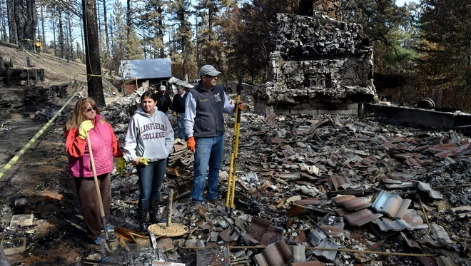 Debbie Sheltra, left, stands at her Franktown Road home that the Little Valley Fire completely destroyed. She's standing with her children Nicole Sheltra Knapp, center, and Ryan Shelra on Oct. 19, 2016. Her kids, who grew up in the home, came to help sort through the rubble to see if anything at all might be salvaged.