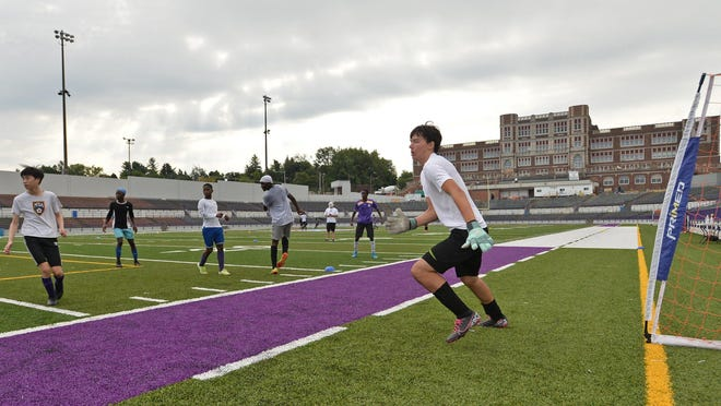 Erie High senior goaltender Stephen Scheppner, center, right, 17, keeps his eye on the ball during a 4-on-4 soccer scrimmage at Veterans Memorial Stadium, Aug. 24, 2020, during the first day of official PIAA sports practices in the Erie region.