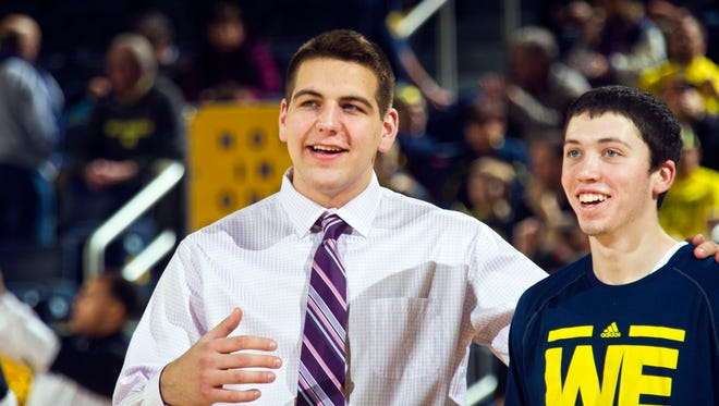 Michigan forward Mitch McGary, left, shares a moment with forward Sean Lonergan, right, before the first half of an NCAA college basketball game against Purdue at Crisler Center in Ann Arbor, Mich., Thursday, Jan. 30, 2014. McGary has taken on a coaching role with the team after undergoing back surgery, with an undetermined recovery period.