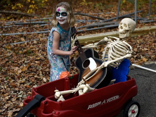 Avery Slade, 7, of Newburgh performs a guitar solo on a float accompanied by a skeleton before the Day of the Dead parade at Wesselman Park Nature Center in Evansville in 2017. The traditional Hispanic holiday focuses on remembering the friends and family of members who have died.