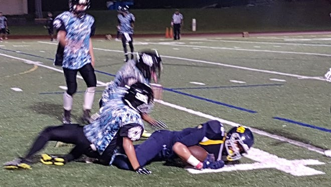 Guam High's Makoa Bamba is tackled by several Dolphins players in their match up on Friday night.