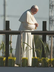Pope Francis stands on an altar facing the U.S. before