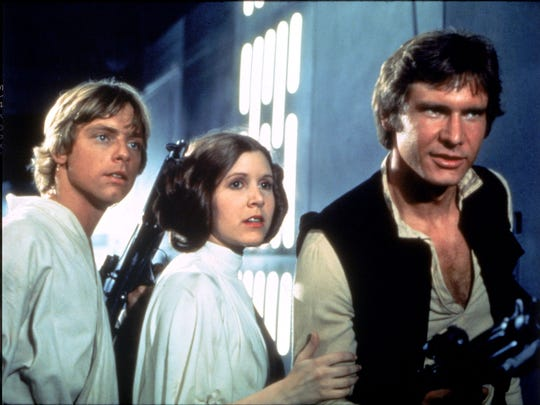 Disney Legends Mark Hamill, left, as Luke Skywalker, and Carrie Fisher as Princess Leia Organa, along with Harrison Ford as Han Solo in 1977's original 'Star Wars.'