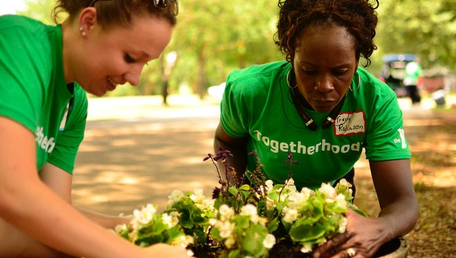 Volunteers from the GHS Family YMCA's Togetherhood program plant flowers at the Church of God Home for Children.