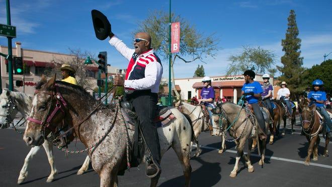 John Goodie waves his cowboy hat while riding a horse during the 2015 Mesa MLK Celebration parade.