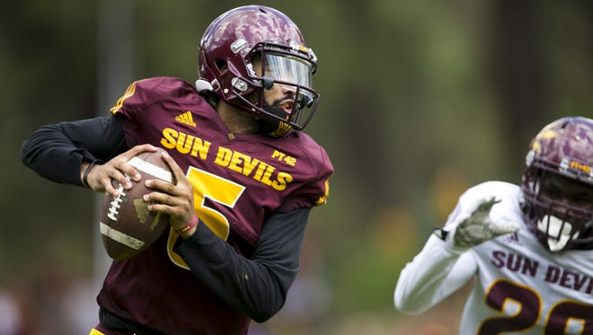 ASU quarterback Manny Wilkins looks down field as he is pursued by ASU safety Jayme Otomewo during an ASU football scrimmage at Camp Tontozona in the Tonto National Forest outside of Payson on August 15, 2015.