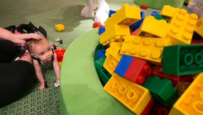 Fourteen-month-old Noelle Conway, of Glendale, looks at giant Lego blocks with her mom, Jaune Farrar, during a sneak peak at the Legoland Discovery Center at Arizona Mills mall in Tempe.