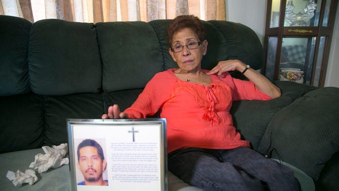 Doris Yamashita Concepcion holds a photograph of her son Joseph Anthony Quinata at her home in Prescott, Ariz., on Thursday, May 26, 2016. Doris alleges that her son was molested by Archbishop Anthony Apuron when he was an altar boy in Guam some forty years ago. Quinata told Doris about being molested by Apuron just before he went into surgery for intestinal perforation in 2005. He did not survive the surgery. Quinata was 38 when he died.