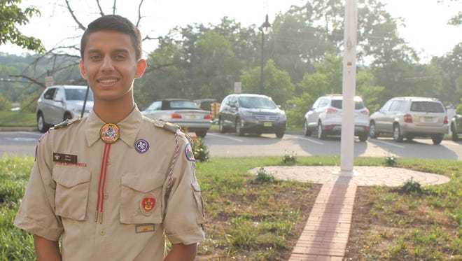 Vraj Shah, 16, donning his troop's uniform, stands proudly in front of Roosevelt Care Center in Edison's flagpole after two days of labor and many months of designing and fundraising.
