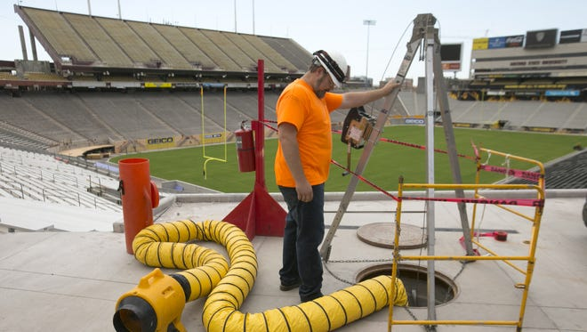 Simon Rohrich, a technician with Sound and Image watches as a fellow construction worker places audio and video wires underground as seen during a tour of Sun Devil Stadium in Tempe on Tuesday, Aug. 23, 2016.