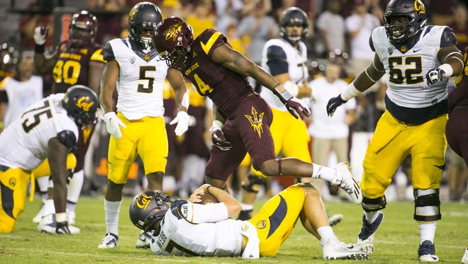 ASU linebacker Koron Crump looks down on Cal quarterback Davis Webb after sacking Webb during the fourth quarter of the college football game at at Sun Devil Stadium in Tempe on Saturday, September 24, 2016. ASU won the game 51-41.
