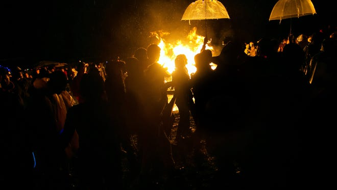 Hundreds of participants gather for a bonfire as they surround the burning wooden pony Saturday at Playa del Fuego in Townsend. Festivities were nearly drowned this year by Hurricane Matthew.