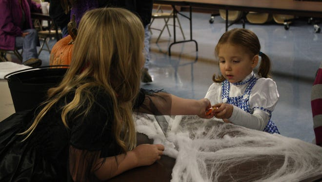 Shyanne Hofmann, 3, of Mcdonough, receives candy during Chenango Forks Fire Company's Trunk or Treat on Sunday.