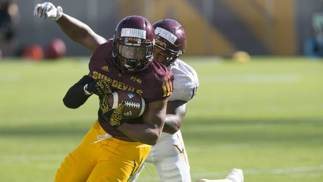 ASU running back Demario Richard carries the ball as as ASU linebacker DJ Calhoun goes in for the tackle during a Spring ASU football practice at Sun Devil Stadium in Tempe on Saturday, March 18, 2017.